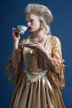 Retro baroque fashion woman wearing gold dress. Holding a cup of tea. Studio shot against blue. photo