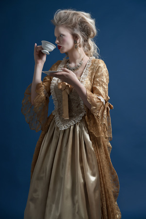 Retro baroque fashion woman wearing gold dress. Holding a cup of tea. Studio shot against blue. Stock Photo