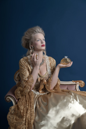 Retro baroque fashion woman wearing gold dress. Holding bottle of parfume. Sitting on vintage couch. Studio shot against blue.