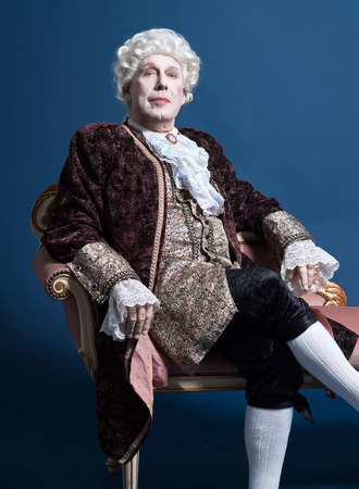 16th century: Retro baroque man with white wig sitting on antique couch. Studio shot against blue. Stock Photo