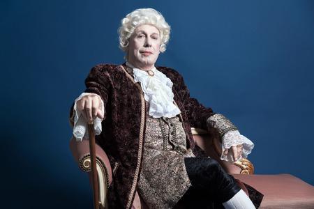 Homem barroco retro com peruca branca, segurando uma bengala sentado no sof� antigo. Est�dio disparado de encontro azul.