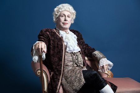 Retro baroque man with white wig holding a walking stick sitting on antique couch. Studio shot against blue.