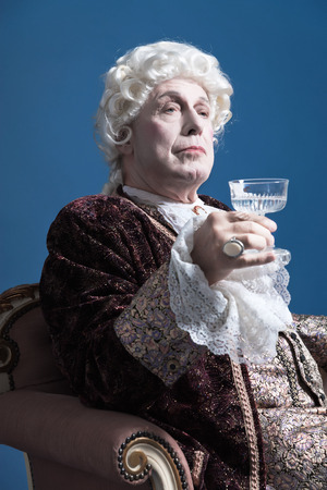 16th century: Retro baroque man with white wig holding a wine glass sitting on antique couch. Studio shot against blue.