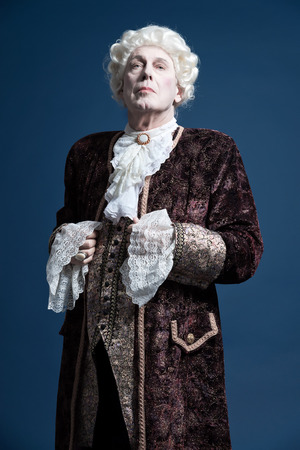 Retro baroque man with white wig standing and looking arrogant. Studio shot against blue. Stock Photo