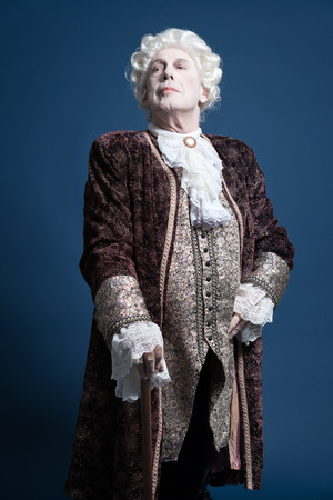16th century: Retro baroque man with white wig standing with walking stick arrogant looking. Studio shot against blue.