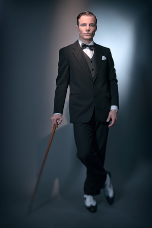 gray suit: Retro 1920 business fashion man wearing black suit and bow tie. Standing with cane. Studio shot. Stock Photo