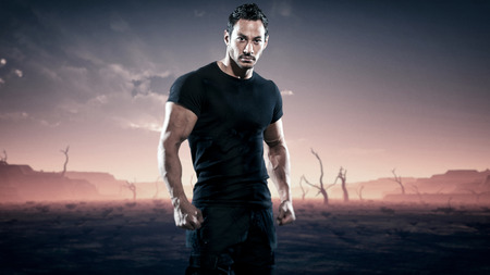 Strong muscled hero fitness man standing in desolate landscape with dead trees. Sunset.