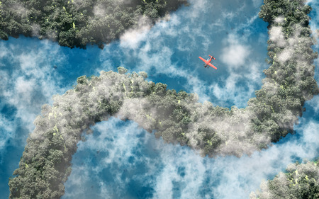 Aerial of red airplane flying over rainforest with river and clouds. photo