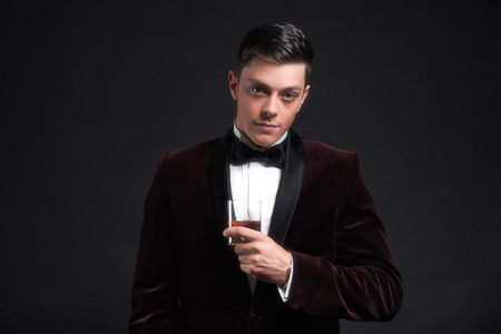 dinner jacket: Well dressed good looking business man holding glass of whiskey. Wearing dark red dinner jacket and black bow tie.