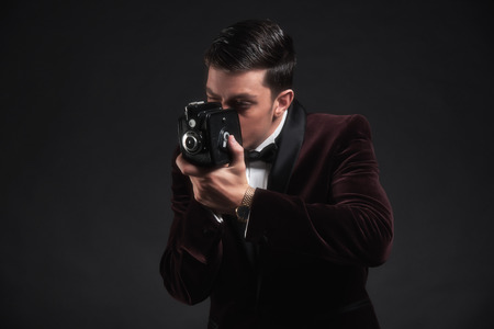 dinner jacket: Well dressed business man taking picture with vintage camera. Wearing dark red dinner jacket with black bow tie.