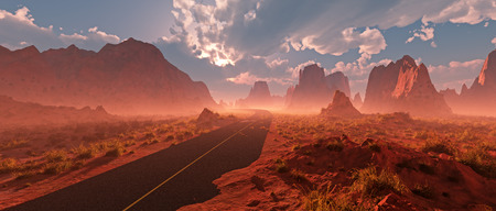 rocky road: Old road through red rocky desert landscape with cloudy sky and mist at sunset. Stock Photo