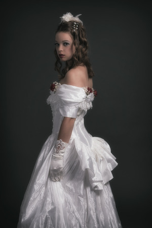 Victorian fashion woman wearing white dress. Studio shot against grey. photo
