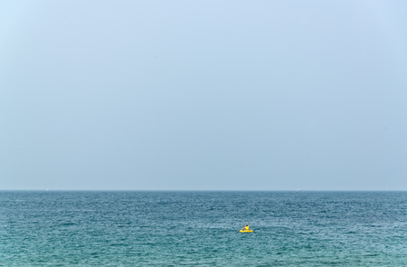 canoeist: Lonely canoeist with yellow kayak in the ocean. Stock Photo