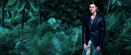 Asian business fashion man in jungle with green ferns and palm trees. Wearing dark grey suit and blue shirt. photo