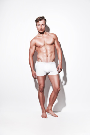 modelos masculinos: Modelo de ropa interior musculoso hombre vistiendo pantalones cortos blancos. Pelo rubio. Contra la pared blanca.