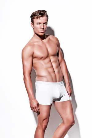 Male muscled underwear model wearing white shorts. Blonde hair. Against white wall. photo