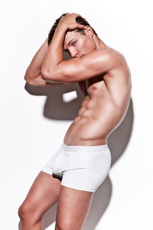Male muscled underwear model wearing white shorts. Blonde hair. Against white wall. Stock Photo