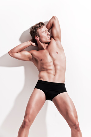young underwear: Male muscled underwear model wearing black shorts. Blonde hair. Against white wall.