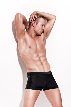 Male muscled underwear model wearing black shorts. Blonde hair. Against white wall. photo