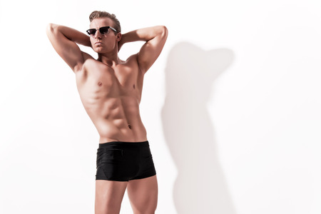 Male muscled underwear model wearing black shorts and vintage sunglasses. Blonde hair. Against white wall. photo