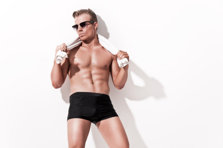 Male fitness underwear model wearing black shorts and vintage sunglasses. Holding white towel. Blonde hair. Against white wall. photo