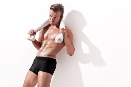 Male muscled underwear model wearing black shorts. Holding white towel. Blonde hair. Against white wall. photo