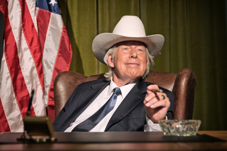 Big boss with white cowboy hat smoking cigar sitting behind desk. American flag in the background. photo