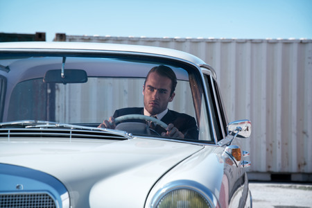 Retro 60s fashion business man wearing grey suit with tie sitting in classic car. photo