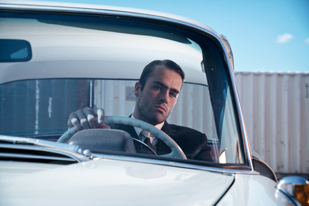 Retro 60s fashion business man wearing grey suit with tie sitting in classic car. Stockfoto