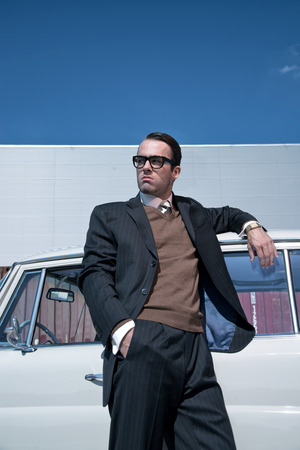 Retro 60s fashion business man wearing grey suit and glasses standing against classic car. photo