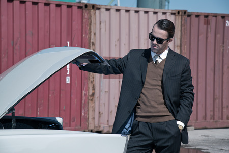 Retro 60s mafia business man with suit and black sunglasses looking in trunk of classic car. photo