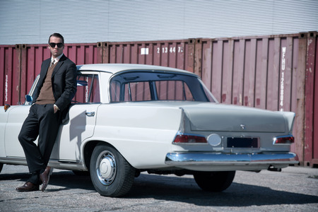 white clothing: Retro 60s fashion business man wearing grey suit and black sunglasses standing against classic car. Stock Photo