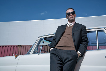 Retro 60s fashion business man wearing grey suit and black sunglasses standing against classic car. photo