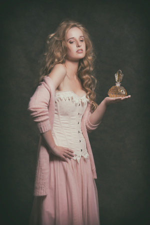 Vintage fashion woman holding old perfume bottle. Wearing pink corset with dress. Studio shot. photo