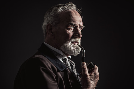 smoking pipe: Pipe smoking vintage characteristic senior man with gray hair and beard. Studio shot against dark background.