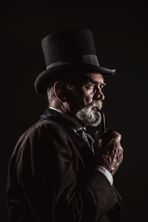Pipe smoking vintage victorian man with black hat and gray hair and beard. Studio shot against dark background.
