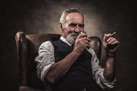 hombre fumando: En silla de salón hombre de negocios de alto con el cigarro y el whisky. El pelo gris y barba que llevaba chaleco de rayas azul y corbata. Contra la pared marrón.