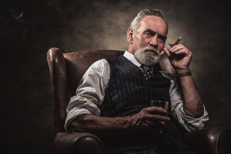 hombre fumando puro: En silla sentado el hombre de negocios de alto con el cigarro y el whisky. El pelo gris y barba que llevaba chaleco a rayas azul y corbata. Contra la pared marrón.