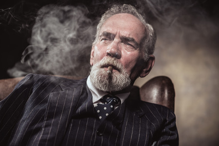 In chair sitting characteristic senior business man. Smoking cigar. Gray hair and beard wearing blue striped suit and tie. Against brown wall. photo