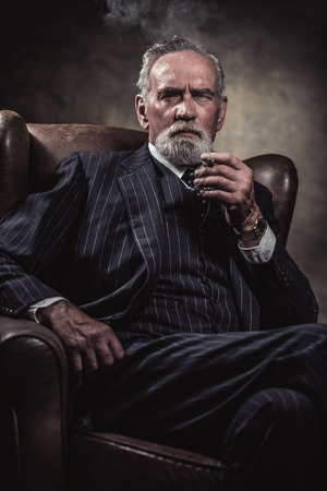 In chair sitting characteristic senior business man. Smoking cigar. Gray hair and beard wearing blue striped suit and tie. Against brown wall. Stock Photo