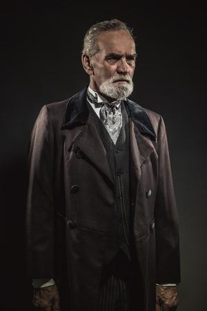 Vintage characteristic senior man with gray hair and beard. Studio shot against dark background. Stock Photo