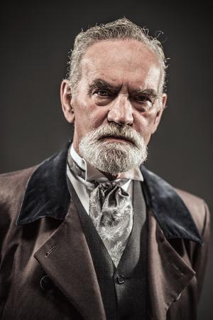 Vintage characteristic senior man with gray hair and beard. Studio shot against dark background. Standard-Bild