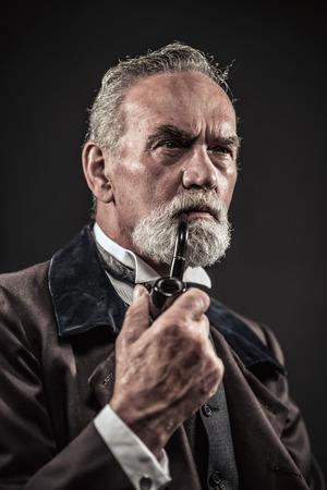 パイプ喫煙灰色の髪と髭を持つヴィンテージの特徴的な年配の男性。スタジオは、暗い背景に撮影。