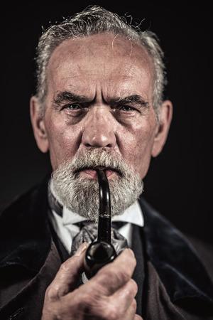 Pfeife rauchen Jahrgang charakteristischen älterer Mann mit grauem Haar und Bart. Studio shot vor einem dunklen Hintergrund. Standard-Bild - 32035060