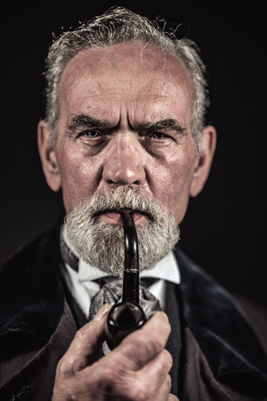 characteristic: Pipe smoking vintage characteristic senior man with gray hair and beard. Studio shot against dark background.