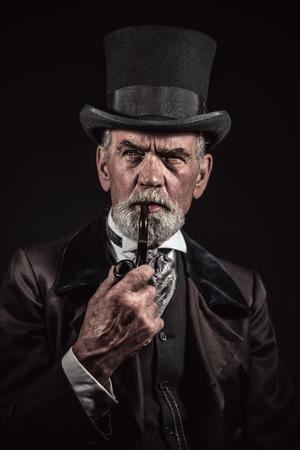 Pijproken vintage Victoriaanse man met zwarte hoed en grijze haren en baard. Studio opname tegen een donkere achtergrond. Stockfoto