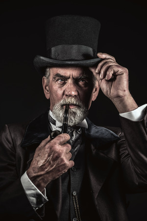 Pipe smoking vintage victorian man with black hat and gray hair and beard. Studio shot against dark background. photo