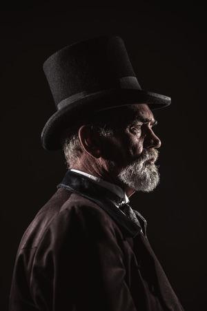 Vintage Victoriaans man met zwarte hoed en grijze haren en baard. Studio shot tegen een donkere achtergrond.