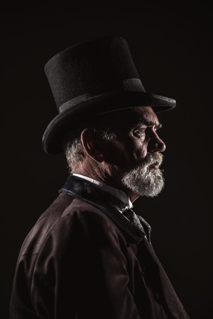 victorian christmas: Vintage victorian man with black hat and gray hair and beard. Studio shot against dark background.