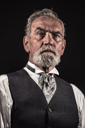 characteristic: Vintage characteristic senior man with gray hair and beard. Studio shot against dark background. Stock Photo